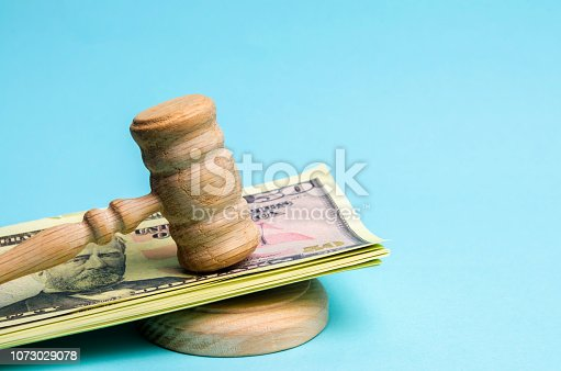 182148217istockphoto US dollars and judge's hammer / gavel. The concept of corruption in the state and government. Court. Bankruptcy, Bribery, Fraud, Crime. Corruption problem in the world. Auction and public sales. 1073029078