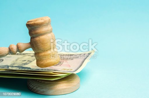 182148217istockphoto US dollars and judge's hammer / gavel. The concept of corruption in the state and government. Court. Bankruptcy, Bribery, Fraud, Crime. Corruption problem in the world. Auction and public sales. 1073029080