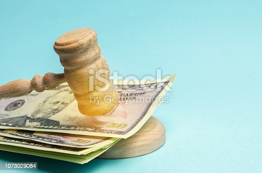 182148217istockphoto US dollars and judge's hammer / gavel. The concept of corruption in the state and government. Court. Bankruptcy, Bribery, Fraud, Crime. Corruption problem in the world. Auction and public sales. 1073029084