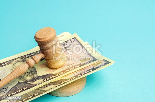 182148217istockphoto US dollars and judge's hammer / gavel. The concept of corruption in the state and government. Court. Bankruptcy, Bribery, Fraud, Crime. Corruption problem in the world. Auction and public sales. 1073029088