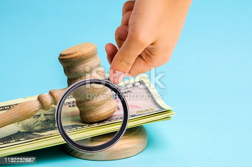 182148217istockphoto US dollars and judge's hammer / gavel. The concept of corruption in the state and government. Court. Bankruptcy, Bribery, Fraud, Crime. Corruption problem in the world. Auction and public sales. 1132232667