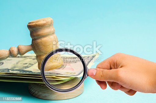 182148217istockphoto US dollars and judge's hammer / gavel. The concept of corruption in the state and government. Court. Bankruptcy, Bribery, Fraud, Crime. Corruption problem in the world. Auction and public sales. 1132232668