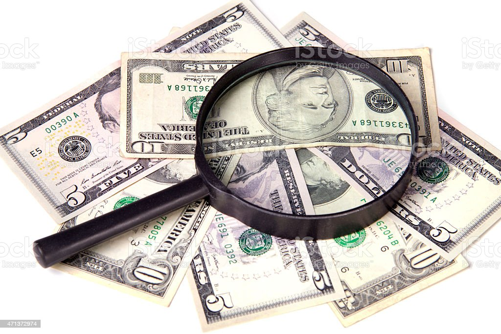 Dollars and magnifying glass on a white background stock photo