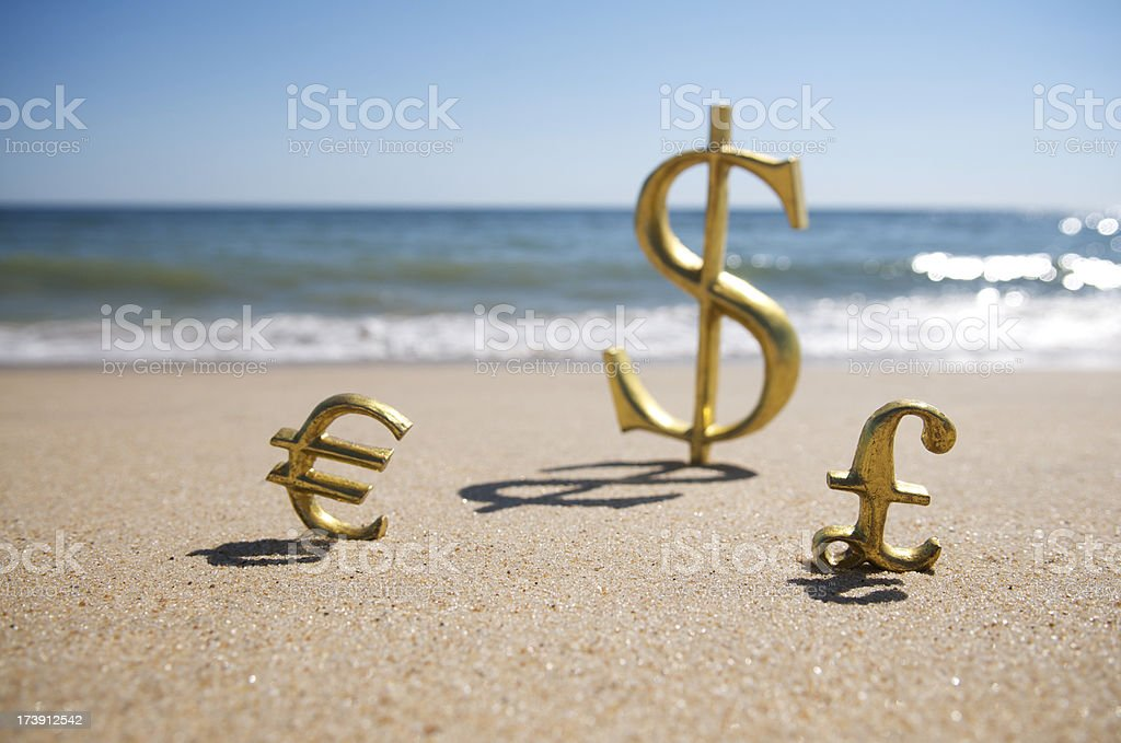 Dollars Euros Pounds Global Currency Sit in Sparkling Sand stock photo