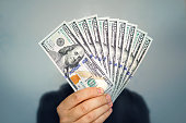 istock 1000 dollars in 100 bills in a man's hand close-up on a dark background. Hands holding dollar cash 1227594879