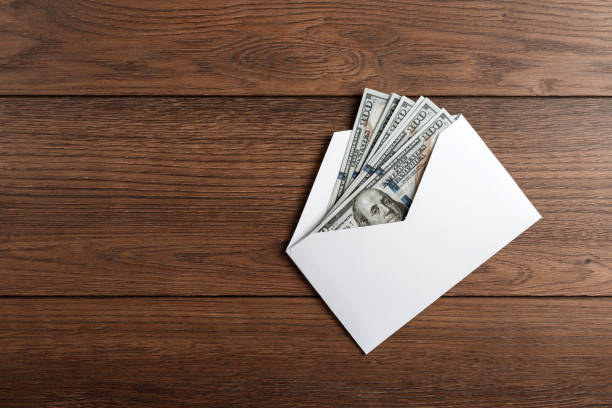 us dollars in a white envelope on a wooden table. the concept of income, bonuses or bribes. corruption, salary, bonus. - bonus foto e immagini stock