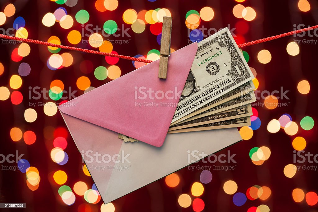 Dollars in an envelope on christmas lights background stock photo