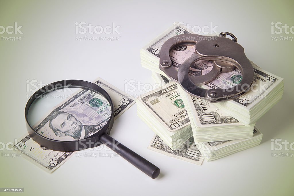 Dollars, magnifier and handcuffs stock photo