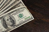 American dollars banknotes on old wooden table background. Dollars money on table.