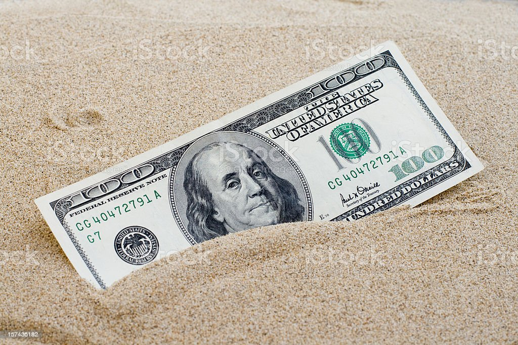 100 dollars sinking in the sand stock photo