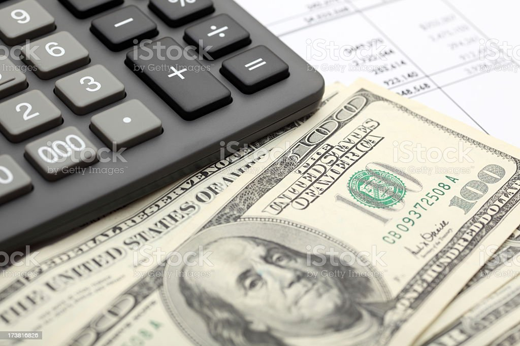 100 dollars with calculator depicting financial statement royalty-free stock photo