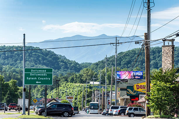 Dollywood Sign in Pigeon Forge Pigeon Forge, USA - June 16, 2016: A road sign for Dollywood amusement park in Pigeon Forge, Tennessee. Cars parked outside other businesses on the right. Various signs. pigeon forge stock pictures, royalty-free photos & images
