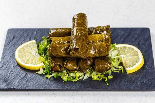 Dolma, stuffed grape leaves with rice and meat Dolma, stuffed grape leaves with rice and meat on black deck. armenian genocide stock pictures, royalty-free photos & images