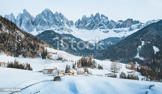 Classic panoramic view of famous Dolomites mountain peaks with the historic village of Val di Funes on a scenic day in winter, South Tyrol, Italy