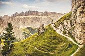 Dolomites scenics view: man hiking in front of the majestic Gruppo del Sella, on the path to Rifugio Stevia