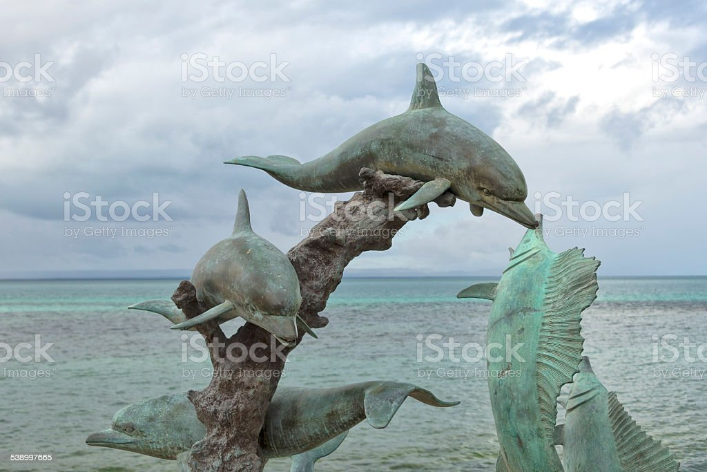 Dolphin copper statue by the sea stock photo