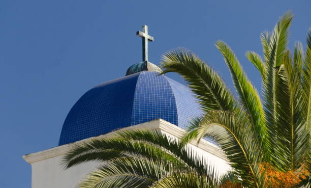 Dome and cross of Immaculate Conception Church next to a palm tree in Old Town, San Diego, California stock photo