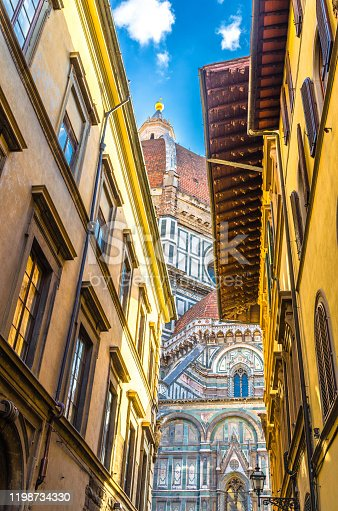 Dome of Florence Duomo, Cattedrale di Santa Maria del Fiore, Basilica of Saint Mary of the Flower Cathedral, buildings on narrow street in historical city centre, view from below, Tuscany, Italy