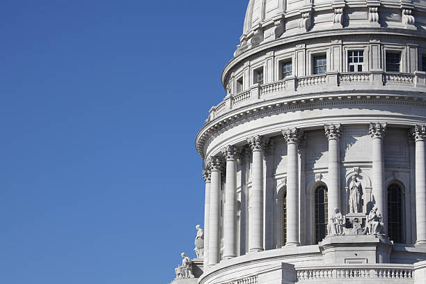 Dome of State Capitol Building with Blue Sky Partial view of a State Capitol building against a blue sky.  wisconsin state capitol stock pictures, royalty-free photos & images