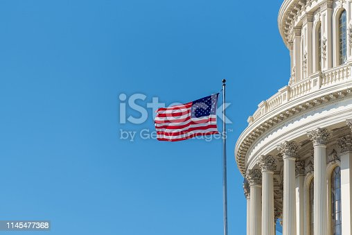 Cupola or dome of the US Capitol building in Washington DC with an American stars and stripes flag flying on a flagpole