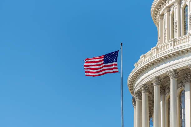 Dome of US Capitol building in Washington DC with American flag stock photo