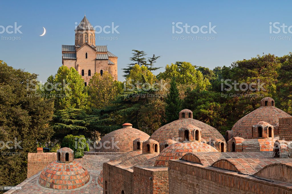 Domes of sulphur baths and Metekhi Church with crescent moon in the sky in Tbilisi, Georgia. stock photo