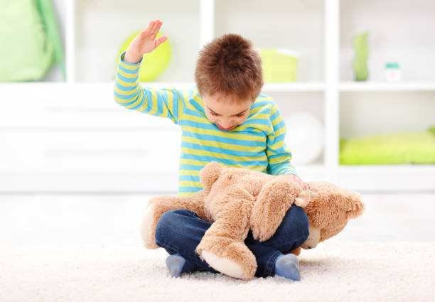 Domestic Abuse Angry little boy beating his teddy bear - domestic abuse concept punishment stock pictures, royalty-free photos & images
