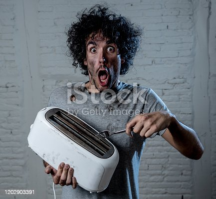 istock Domestic accidents and electricity danger. Young man electrocuted trying to get toast out of toaster with knife. Husband screaming as getting an electric shock with dirty burnt funny face expression. Home Safety concept. 1202903391