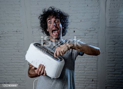 istock Domestic accidents and electricity danger. Young man electrocuted trying to get toast out of toaster with knife. Husband screaming as getting an electric shock with dirty burnt funny face expression. Home Safety concept. 1202905697
