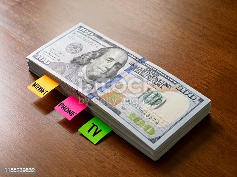 Adhesive notes inside a  pile of 100 dollar bills symbolizing expenses