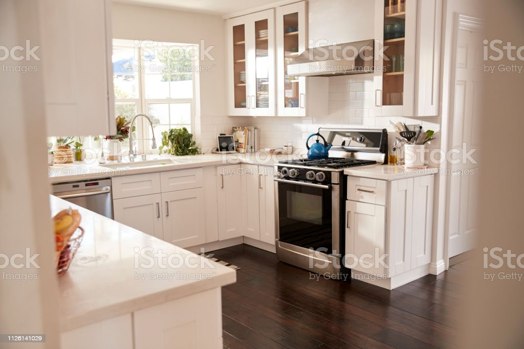 Domestic family kitchen with white furniture and dark wooden floorboards, seen from doorway stock photo
