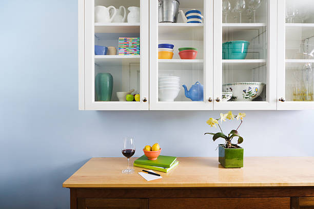 Domestic Kitchen Counter Top and Cabinet Display of Neat Organization A well-organized kitchen cabinet, counter and cupboard, displaying a glass of wine, books, flowers and housewares in a neat, tidy, freshly painted home interior. neat stock pictures, royalty-free photos & images