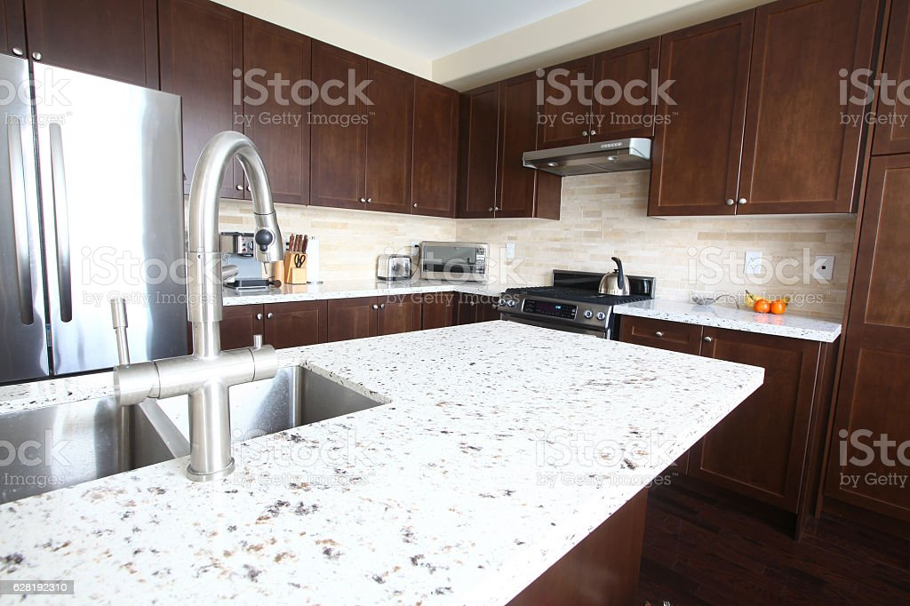 Domestic kitchen with quartz countertops and chestnut cabinets stock photo