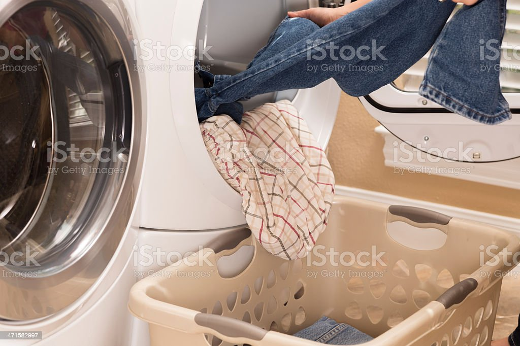 Domestic Life:  House wife removing clothes from dryer.  Laundry basket stock photo