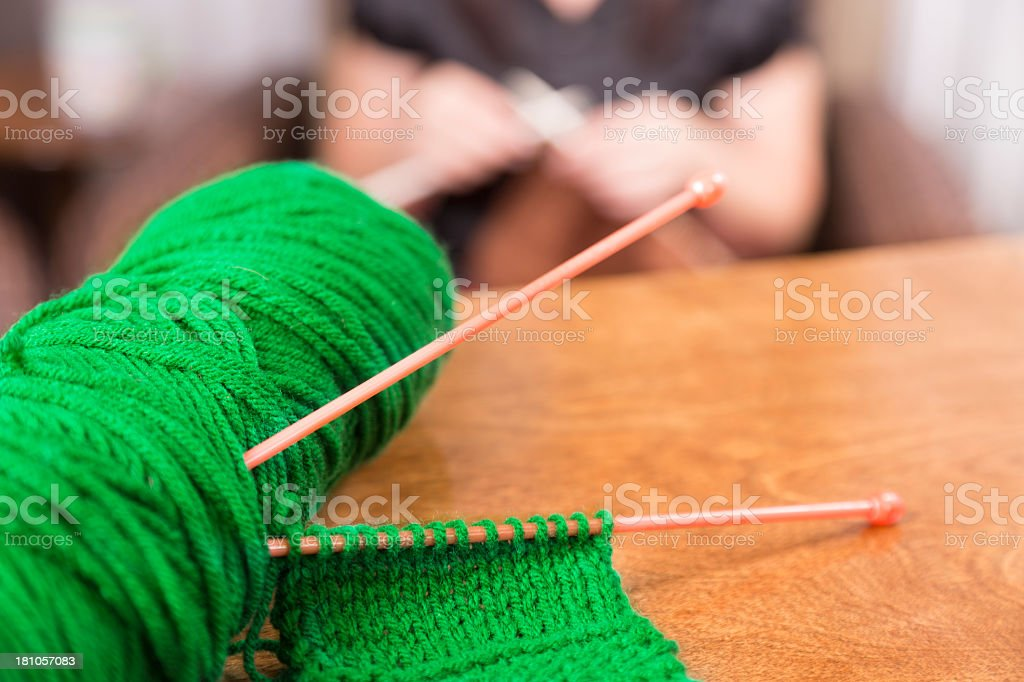 Domestic Life:  Knitting left on dining table.  Woman in background. royalty-free stock photo