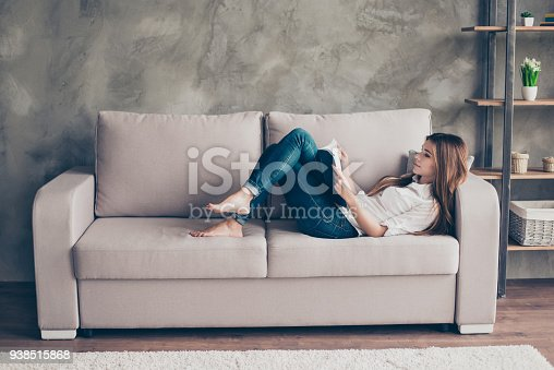 istock Domestic life. Relaxed young lady is studying, lying on the cozy beige couch in living room at home, so nice modern interior, so comfortable atmosphere for study and work 938515868