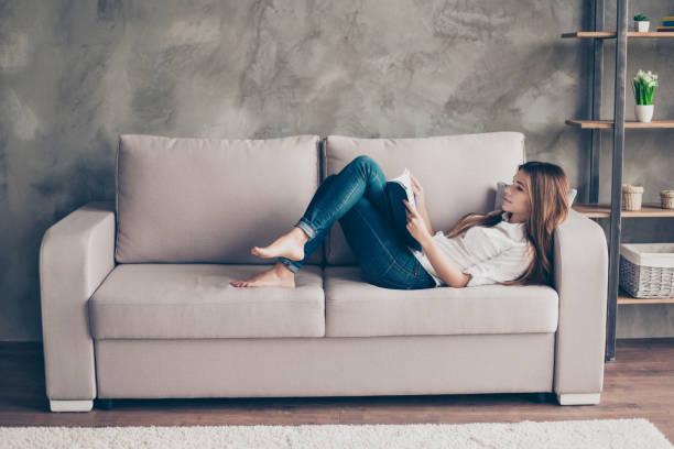 vida doméstica. señora joven relajada es estudiar, mentir en el acogedor sofá beige en la sala de estar en casa, interior moderno tan agradable, tan cómodo ambiente para estudio y trabajo - sofá fotografías e imágenes de stock