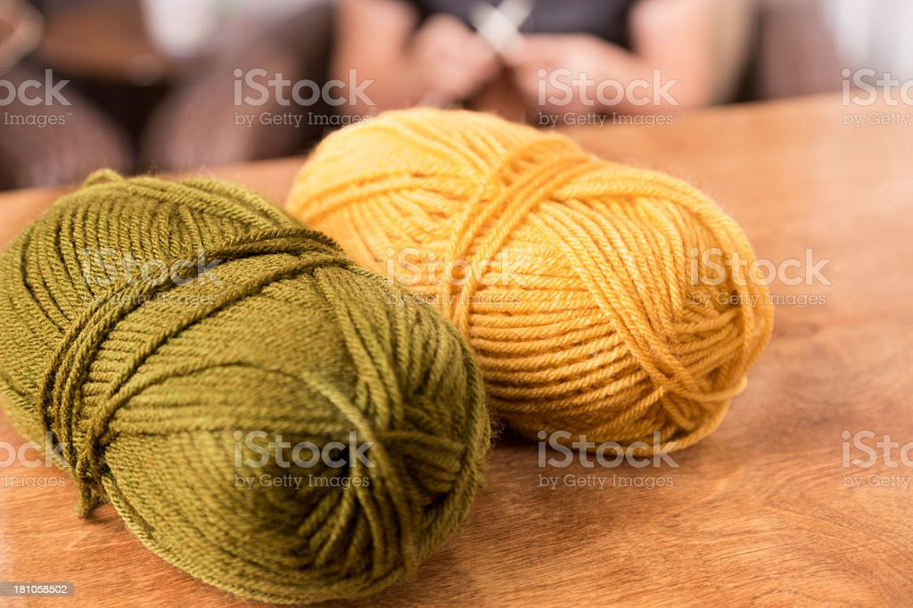 Domestic Life:  Skiens of knitting wool on table.  Woman  background. royalty-free stock photo