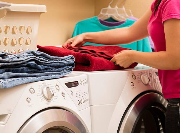 das leben zu hause: frau falten handtücher aus dem trockner. wäschekorb - hausmittel gegen falten stock-fotos und bilder