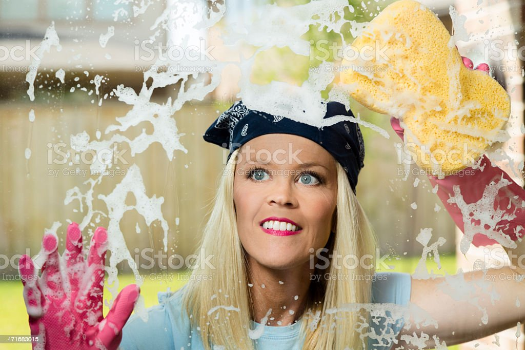 Domestic Lifestyle: Woman washing her windows. royalty-free stock photo