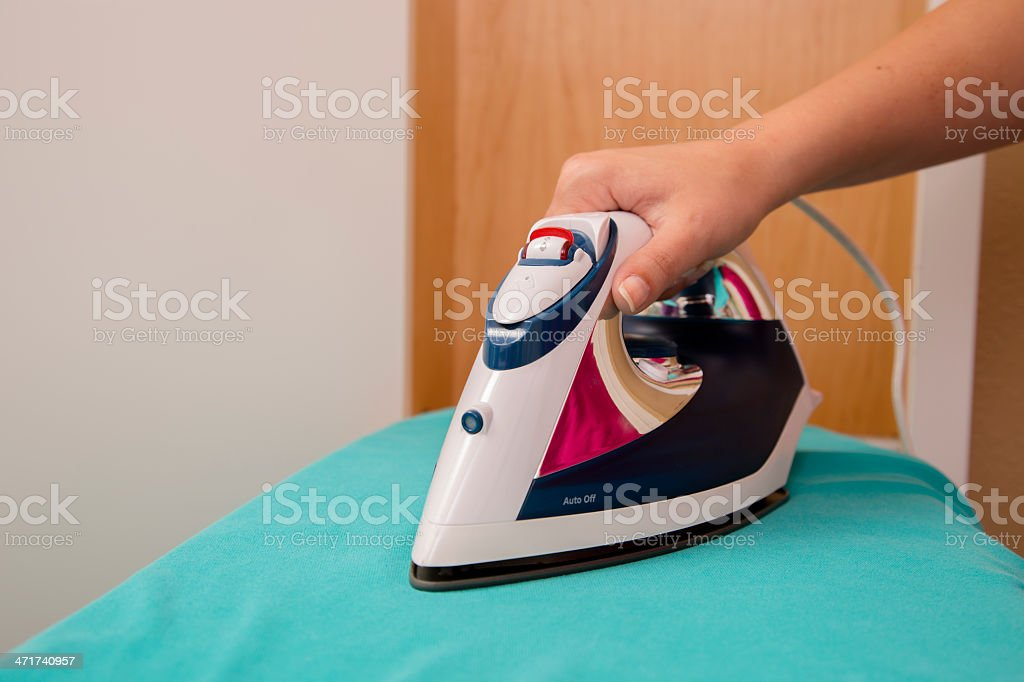 Domestic Lifestyle:  Young woman pressing blouse on the ironing board. royalty-free stock photo