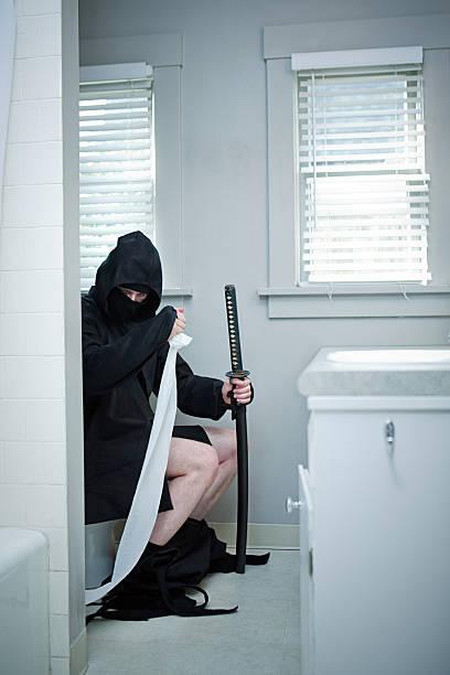 domestic ninja auf der toilette - ninja krieger stock-fotos und bilder