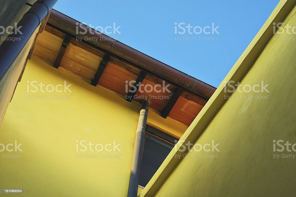 Domestic rooftop detail, yellow on blue sky background - Drain royalty-free stock photo