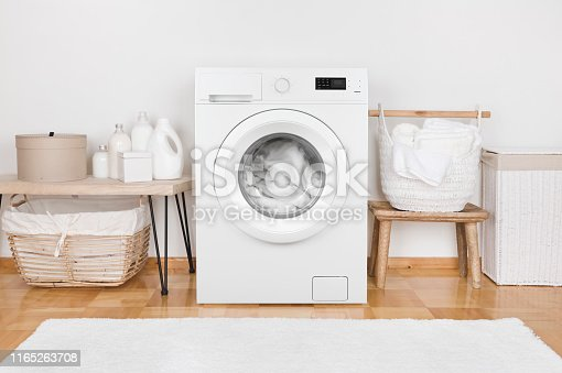 istock Domestic room interior with modern washing machine and laundry baskets 1165263708