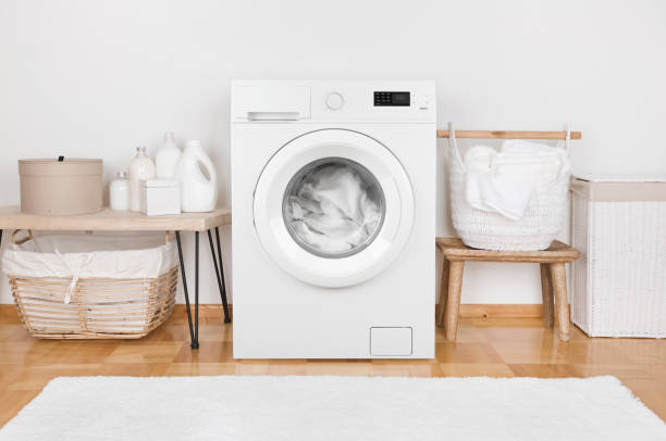 Domestic room interior with modern washing machine and laundry baskets stock photo