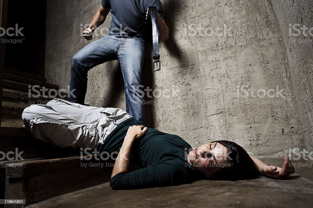 Domestic violence against women with man beating with belt stock photo