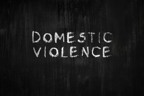 Domestic violence phrase handwritten on black wood background. stock photo
