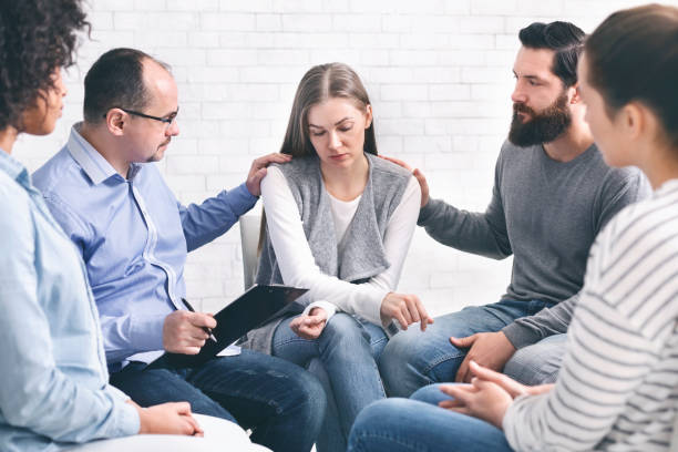 Domestic violence victim on therapy with support group Domestic violence victim. Stressed woman sharing her problems on therapy with support group, free space drug rehab stock pictures, royalty-free photos & images