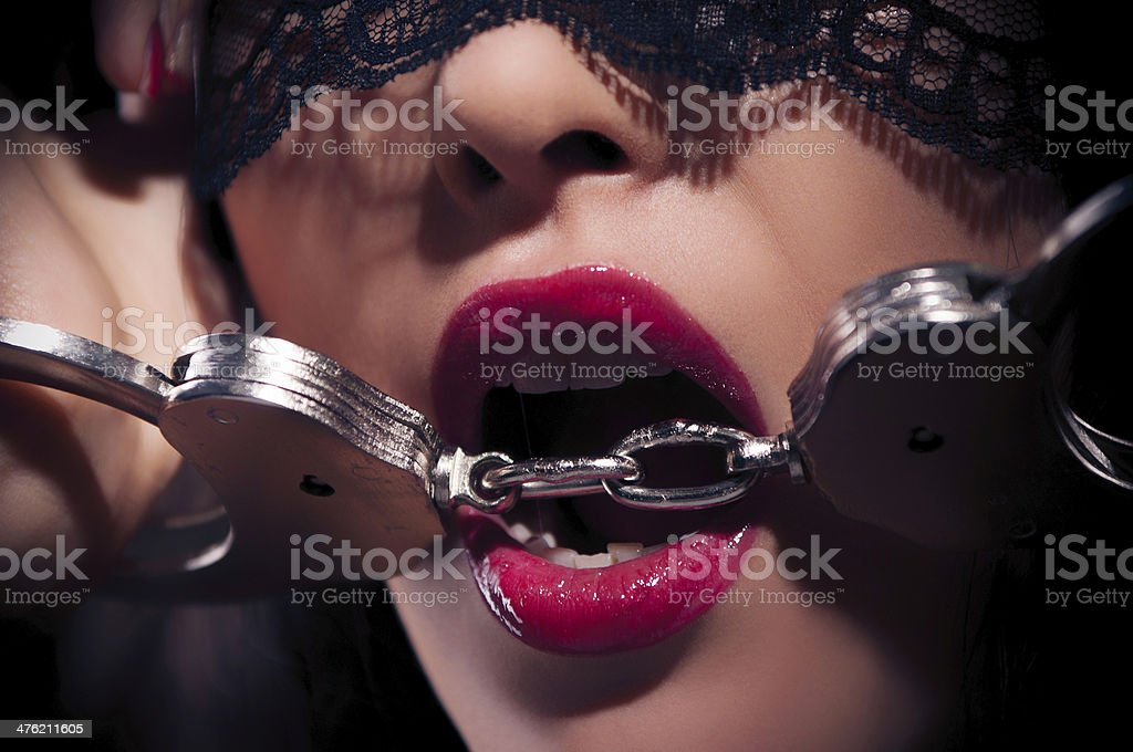 Dominating beauty in handcuffs stock photo