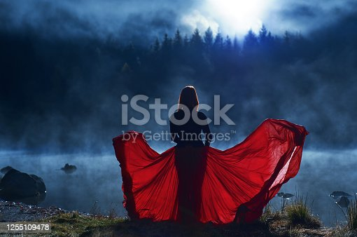 Dominating woman at the lake posing in flying red skirt at sunset